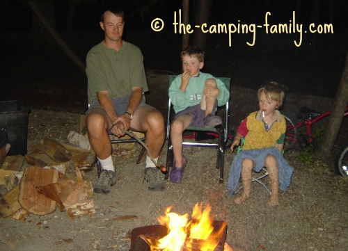 family roasting hot dogs around the campfire