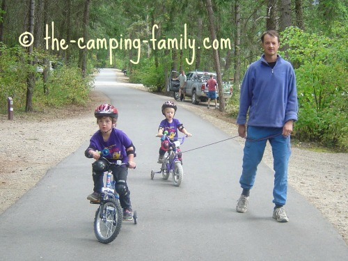 dad and boys biking on paved campground roads