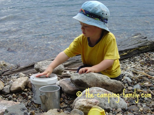 small boy playing with rocks and a bucket