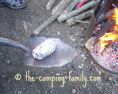 foil wrapped potato on a spade