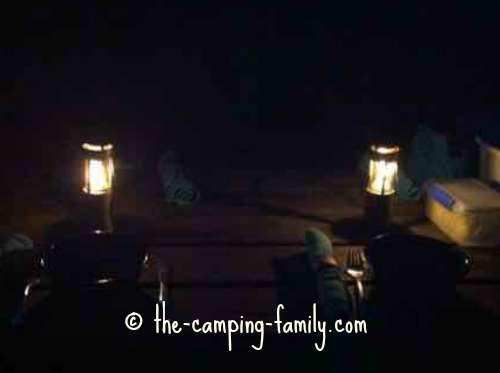 two candle lanterns on picnic table