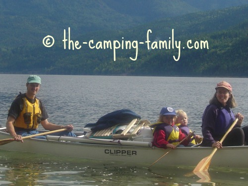 family in canoe with folding chairs lashed to pile of gear