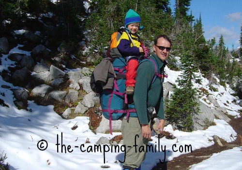 child riding on top of dad's backpack