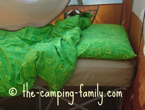camping cot with pillow and duvet, in tent