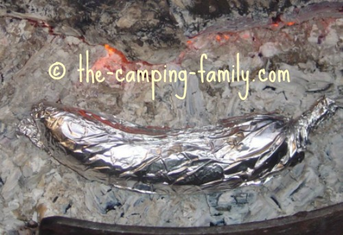 foil-wrapped banana in the coals