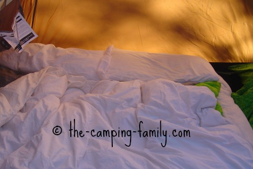 air bed with sheets and duvet, in tent