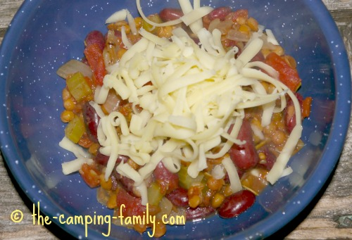 Lentil Skillet Supper in bowl with grated cheese