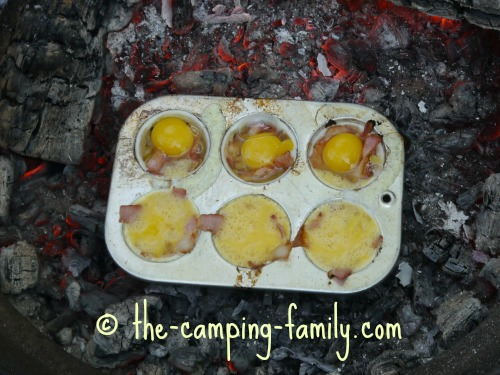muffin tin bacon and eggs cooking on campfire