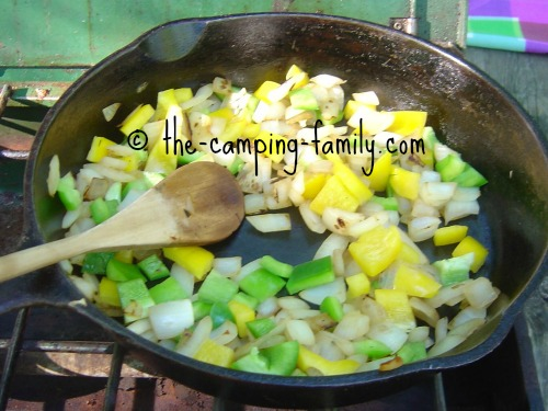 onions and peppers in skillet