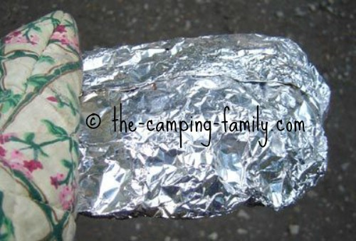 holding foil packet with oven mitt