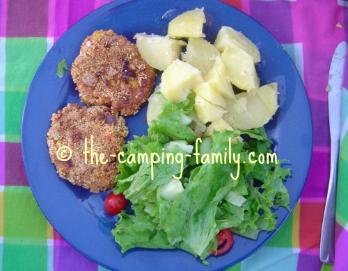 salmon patties on plate with salad and boiled potatoes