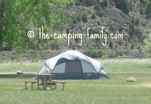 tent in sunny campground with trees