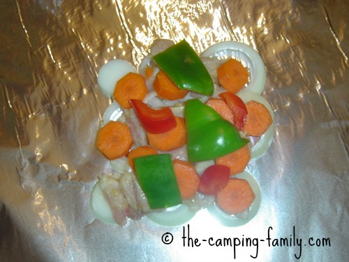 chicken onion carrots and peppers on foil