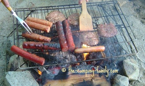 burgers and hotdogs on a grill over a campfire
