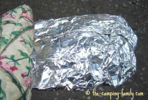 holding foil dinner with oven mitt