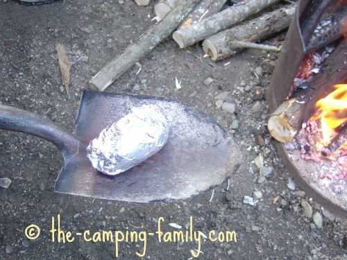 removing foil-wrapped potato from campfire with spade