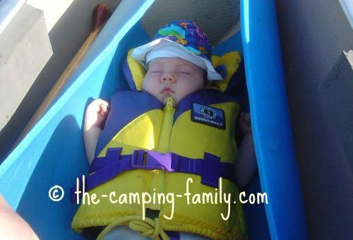 baby in life jacket sleeping on foam pad in canoe