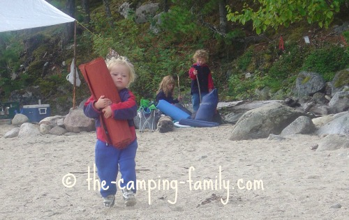 young child carrying Thermarest