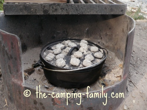 Dutch oven in fire pit with coals on lid
