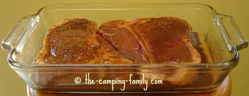 steak marinating in a glass pan