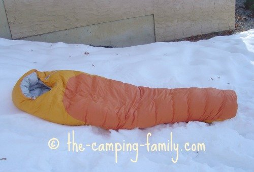 orange down sleeping bag on snow