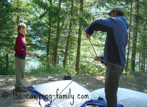 father and son pitching a tent