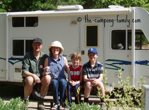 family in front of travel trailer