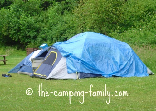 tent draped with blue tarp